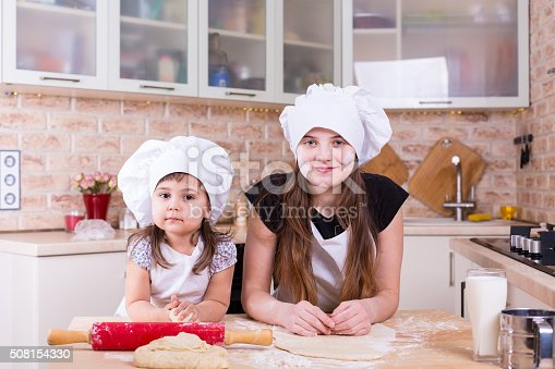 488109116istockphoto two sisters making dough at home 508154330