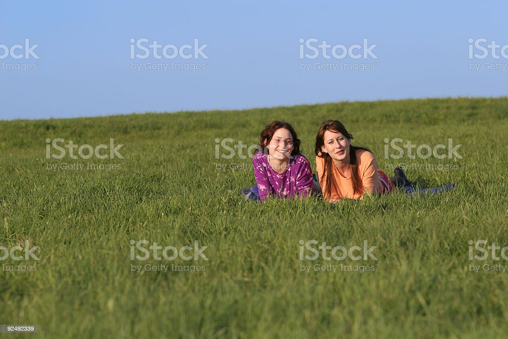 Two sisters on a big green field royalty-free stock photo
