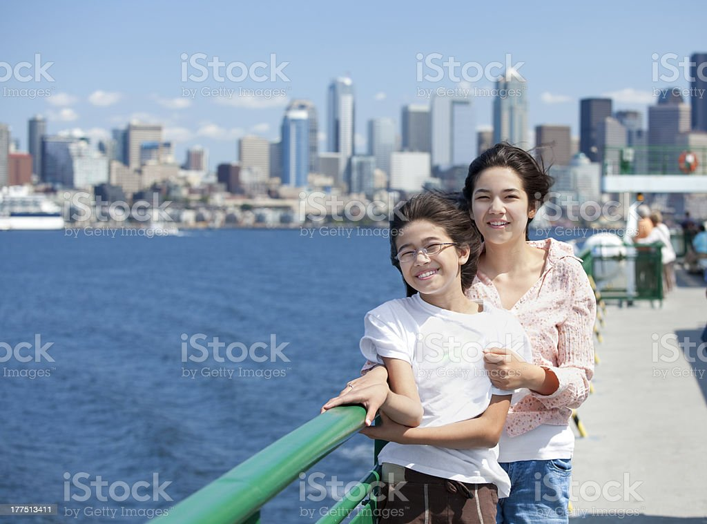 Two sisters on ferry deck with Seattle skyline in background stock photo