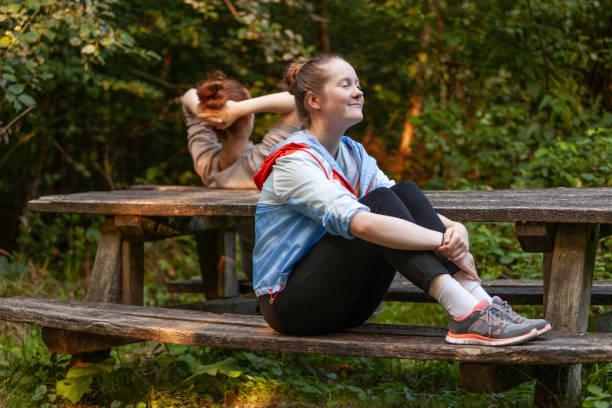 Two sisters out in the woods, at a picnic table, resting after a jogging session stock photo