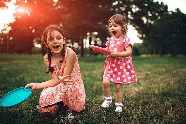 zwei schwestern spielen frisbee auf picknick - kinder picknick spiele stock-fotos und bilder