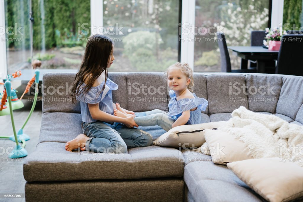 two sisters playing together on the big couch Lizenzfreies stock-foto