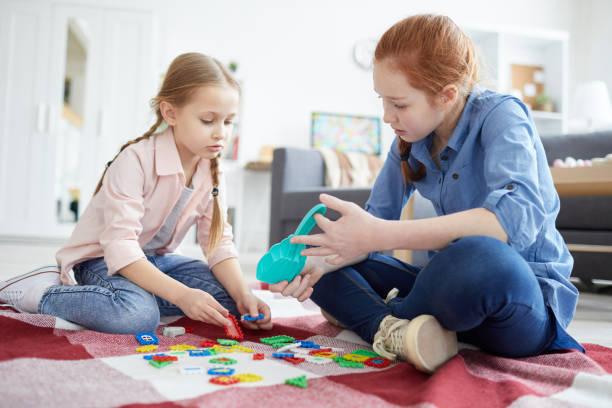 dos hermanas jugando juntas - niñera fotografías e imágenes de stock