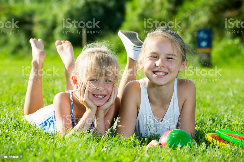 Duas irmãs descansando na grama verde - foto de acervo