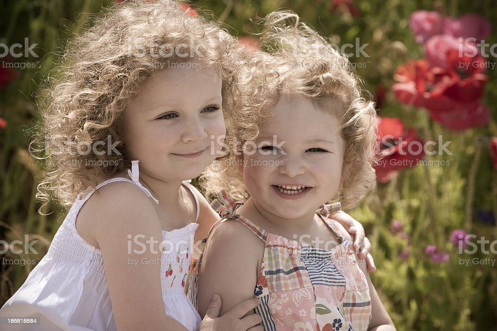 Two sisters sit in a poppy field royalty-free stock photo