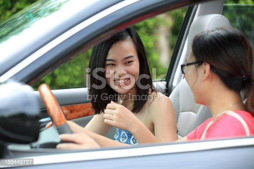 907987862 istock photo Two sisters siting talking in the car 155443727