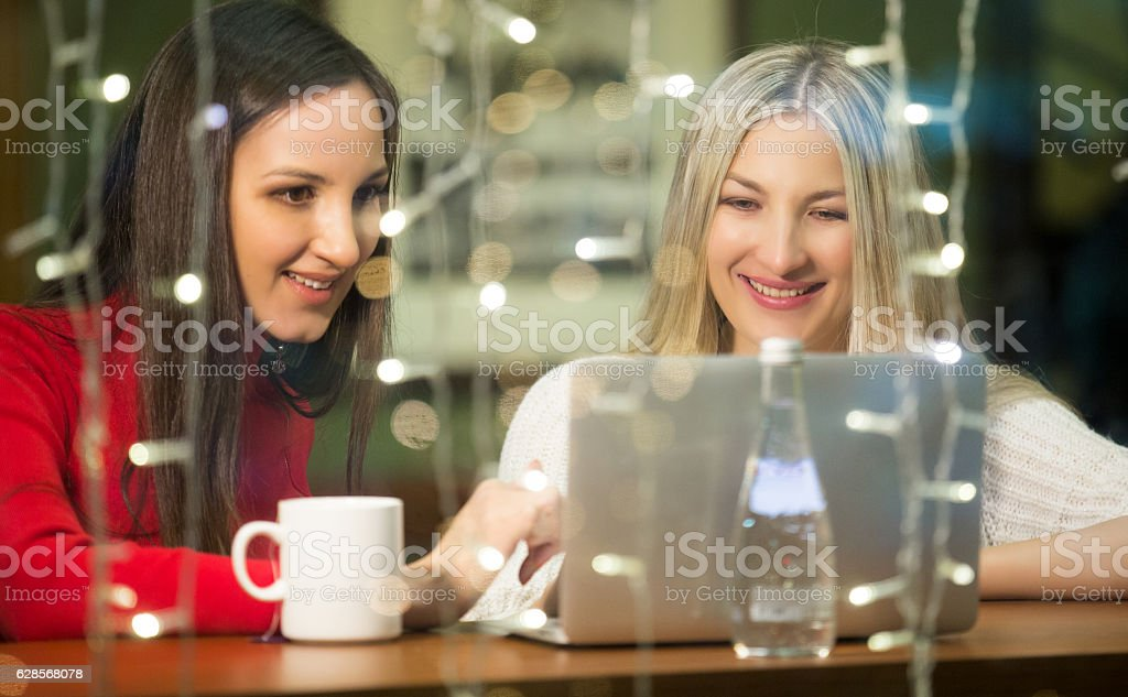 Two sisters sitting in cafe at the window stock photo
