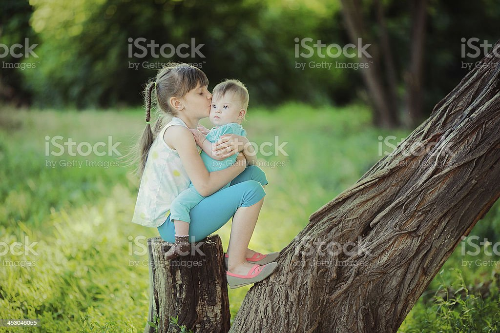 two sisters sitting on a tree in park royalty-free stock photo