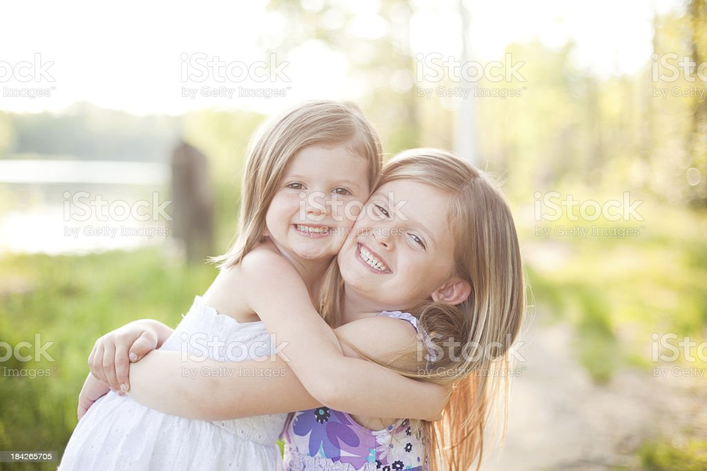 Two Sisters Smiling and Hugging royalty-free stock photo