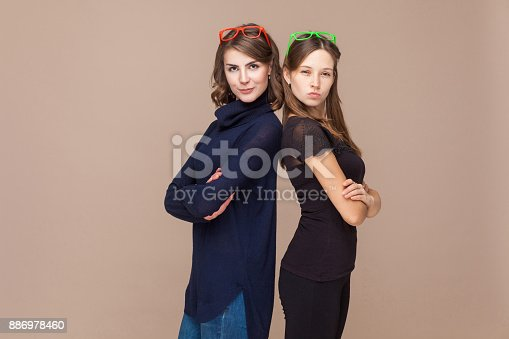 istock Two sisters standing back to back and looking at camera seriously 886978460