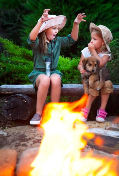 two sisters talking stories by the campfire - geschichten für kinder stock-fotos und bilder