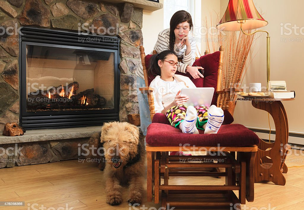Teenager girl sitting in the armchair and playing with tablet in the...