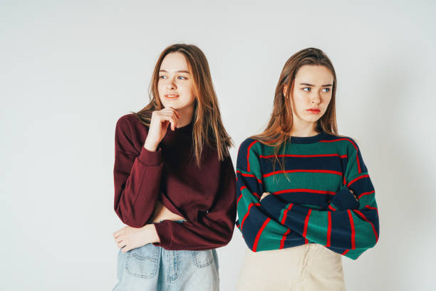Two sisters twins beautiful girls hipsters in casual clothing an Two sisters twins beautiful girls hipsters in casual clothing antipodes smiling and sad on grey background isolated antipode stock pictures, royalty-free photos & images
