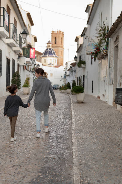 Dos hermanas caminando de la mano por el pueblo de Altea. - foto de stock