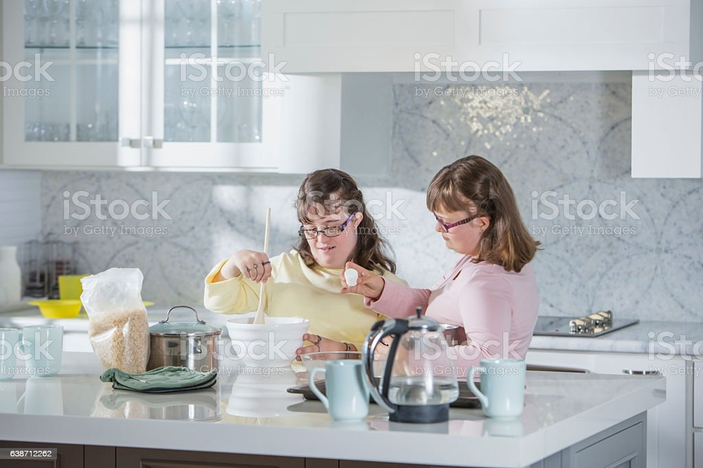 Two Sisters With Down Syndrome In The Kitchen Stock Photo ...
