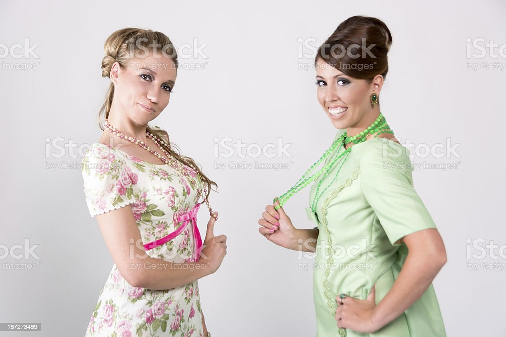 Two sixtys styled women distracted from conversation. stock photo