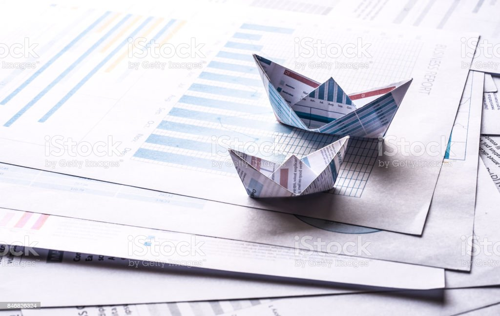 Two Size of boats made with paper graph on business document...