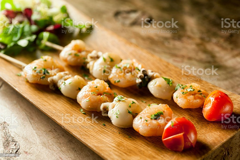 Two skewers of seafood salad on wooden base Two skewers of seafood salad on wooden base Backgrounds Stock Photo