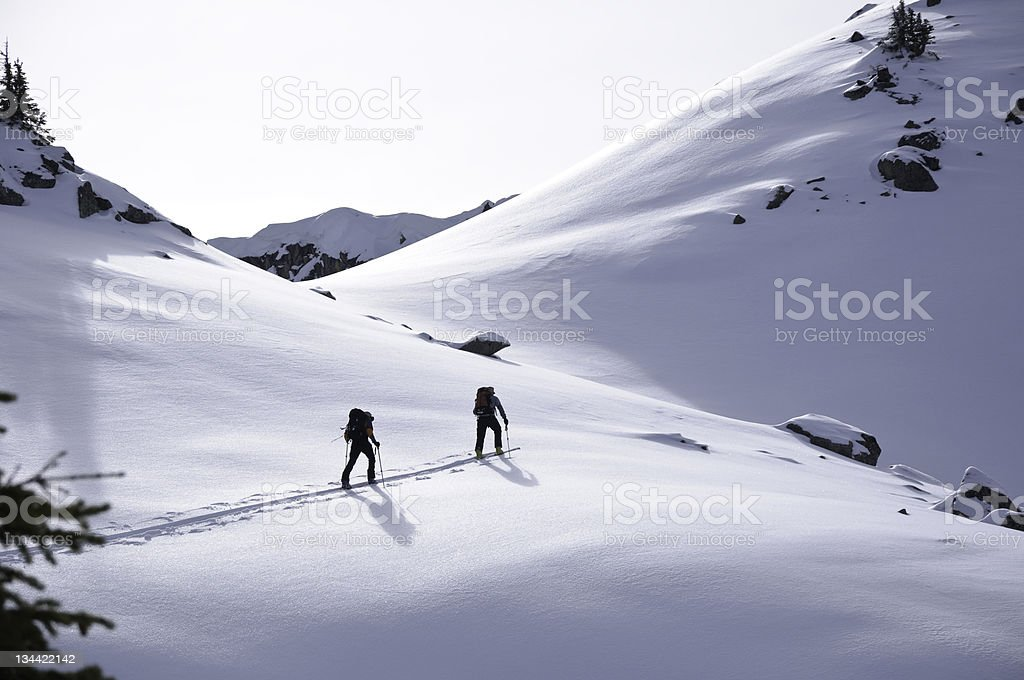 Two Ski Touring Skiers Approach Mountain Pass royalty-free stock photo