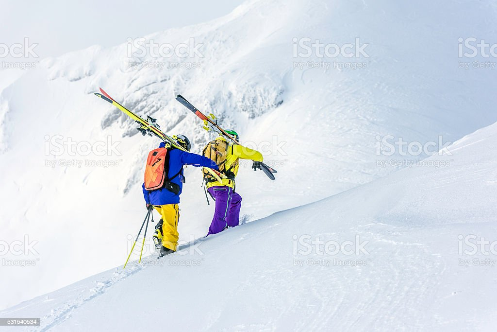 Two skiers climbing up a snowy hill stock photo