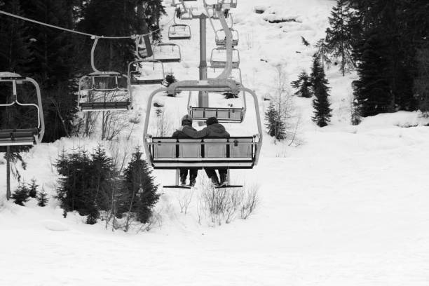 Two skiers on chair-lift in gray day - foto stock