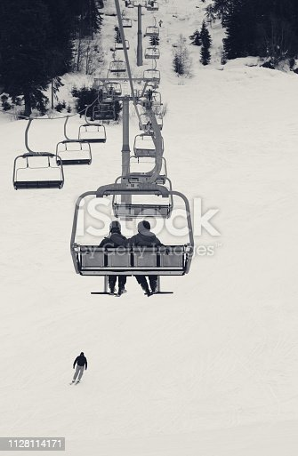 Two skiers on chair-lift in gray winter day. Caucasus Mountains. Hatsvali, Svaneti region of Georgia. Black and white toned landscape.