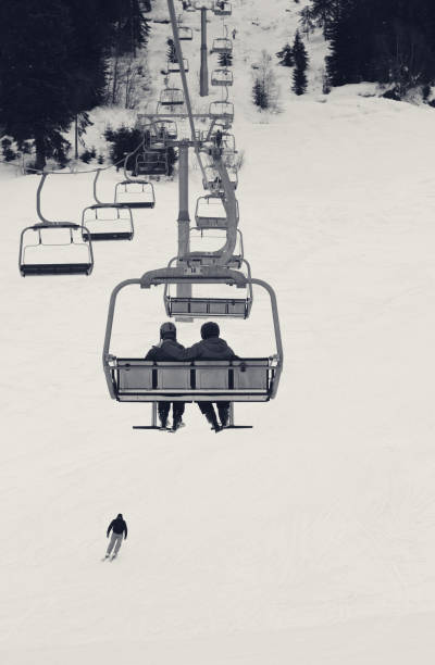 Two skiers on chair-lift in gray winter day - foto stock