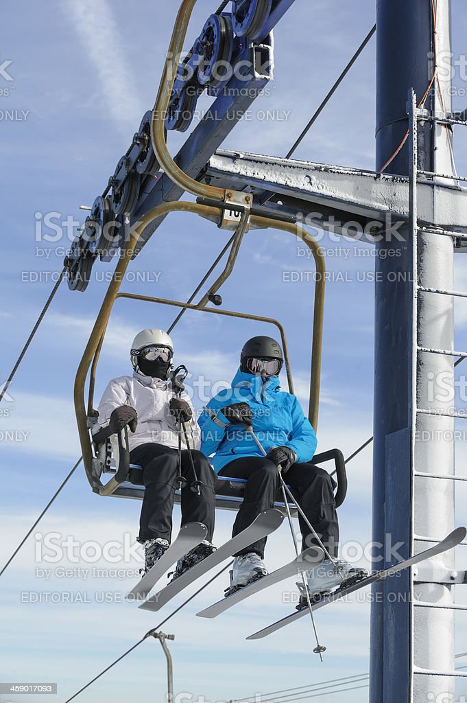 Two Skiers Riding Ski Lift, Man and Woman Close Up stock photo