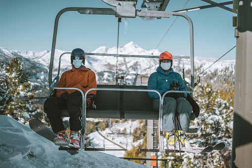 two skiing people, man and woman wearing mouth nose mask on chair ski lift with social distance on sunny winter day in the mountains