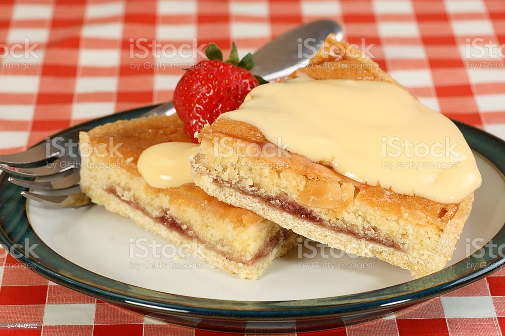 two slices of bakewell tart with custard stock photo