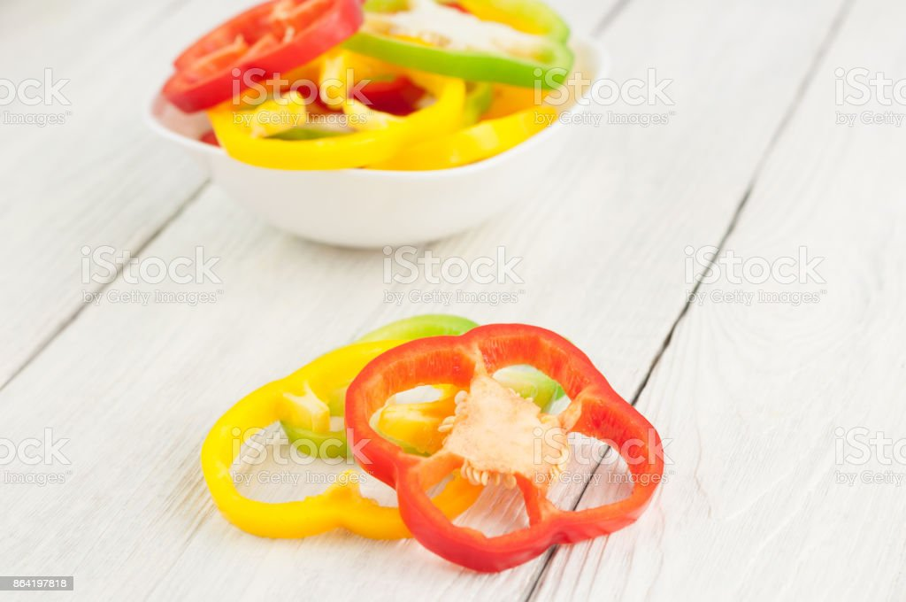 Two slices of colored red and yellow fresh ripe raw pepper beside heap of slices of pepper in ceramic bowl on old rural white wooden planks royalty-free stock photo