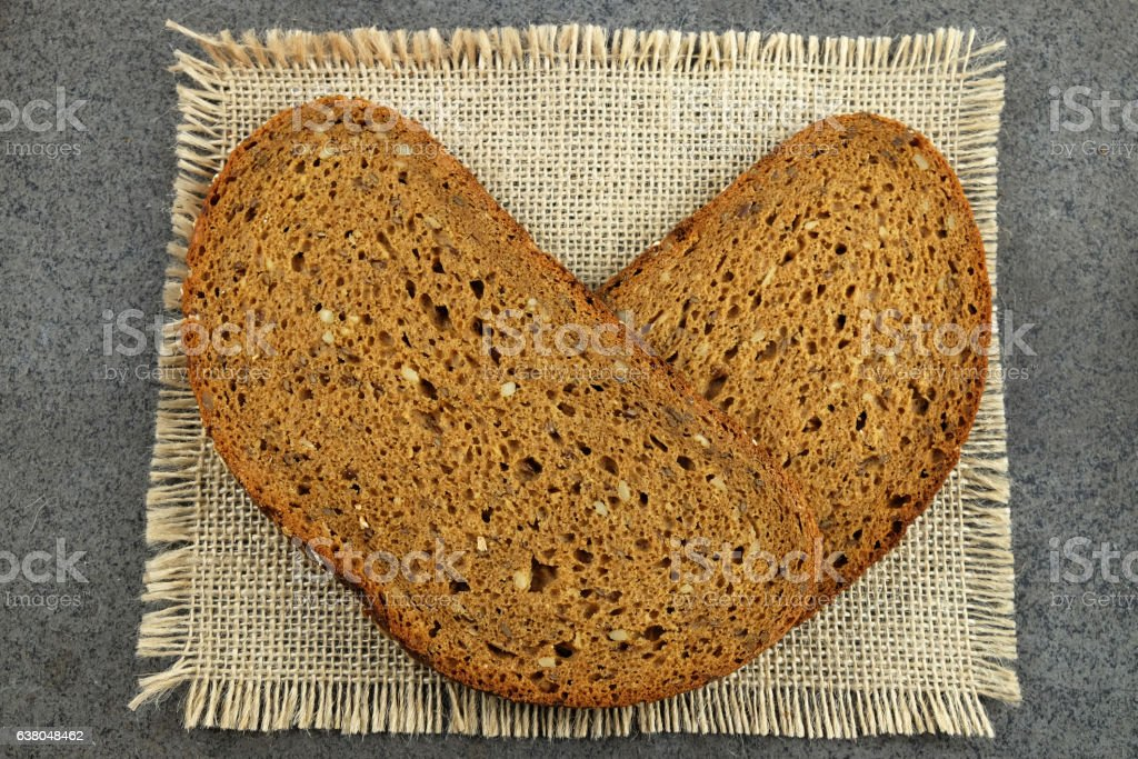 Two slices of grain bread in the shape of heart. stock photo