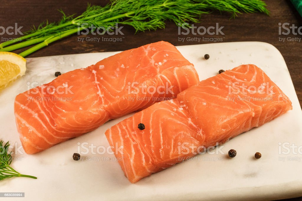 Two slices of salmon on dark background with drill sprigs foto de stock royalty-free