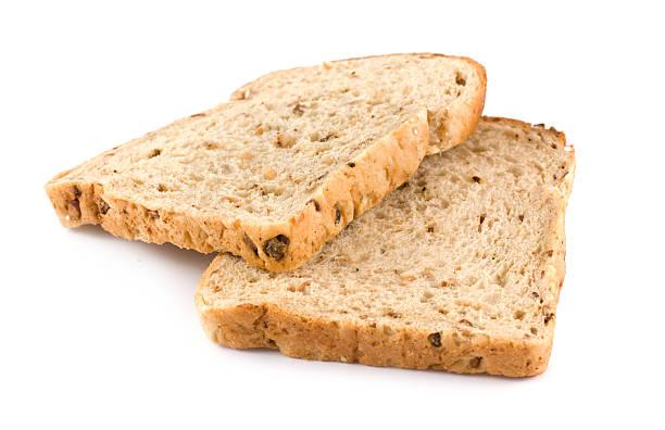 dos rodajas de wholemeal pan marrón sobre un fondo blanco - pan multicereales fotografías e imágenes de stock