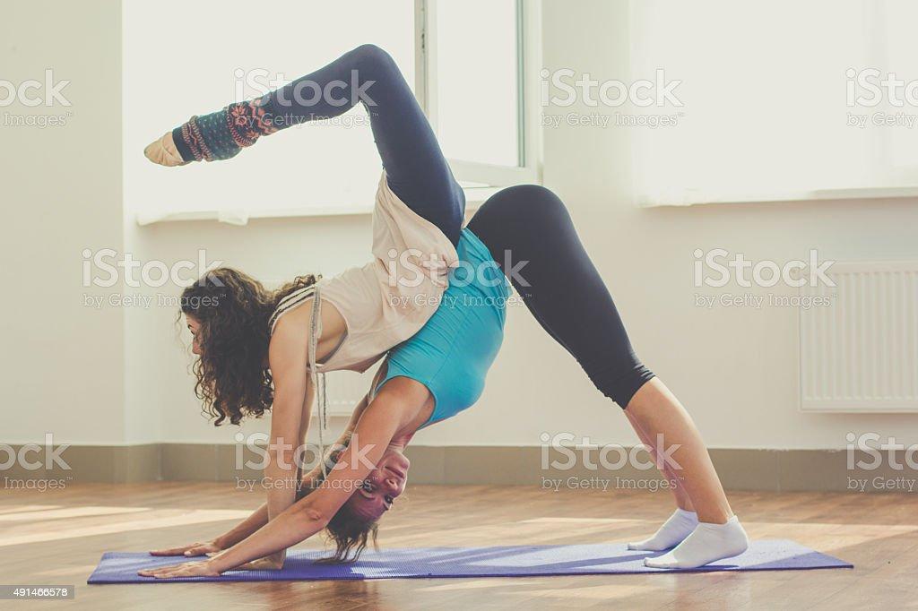 Dos chicas estrecho están haciendo yoga en el interior foto de stock libre  de derechos 5fe8d688683b
