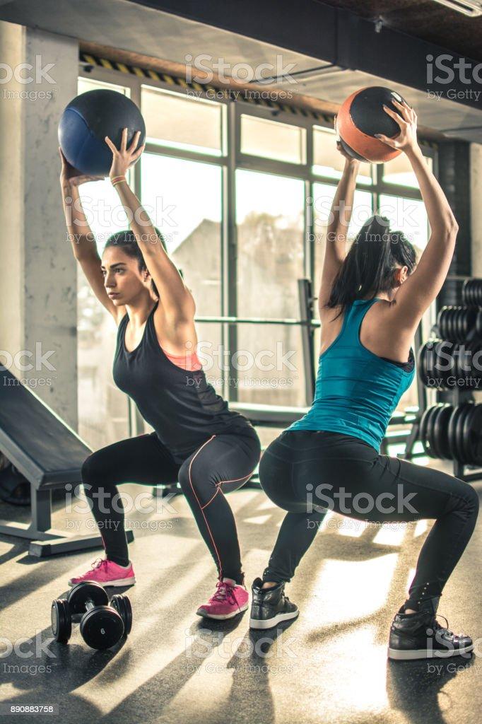 twee slanke sportieve meisjes trainen met fitness ballen in de