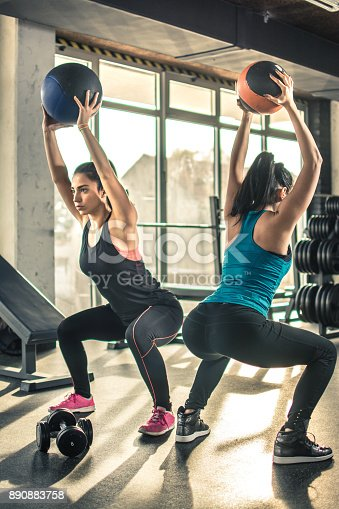 istock Two slim sporty girls exercising with fitness balls in the gym. 890883758