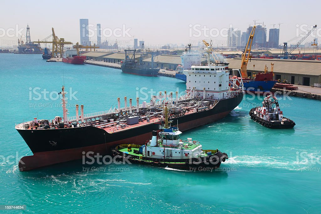 Two small boats docked to industrial ship in port royalty-free stock photo