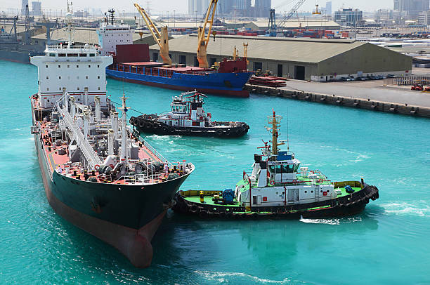 Two small boats docked to industrial ship in port stock photo