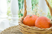 istock Two Small Bright Orange Heirloom Red Kuri Pumpkins in Wicker Basket Dry Autumn Plants on Rattan Table on Cottage Terrace. Cozy Early Fall Atmosphere. Kinfolk Hygge. Thanksgiving. Copy Space 1009013628