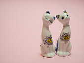 two small ceramic cats both woman on pink background. heads tilted to each other. love story concept. same gender marriage invitation