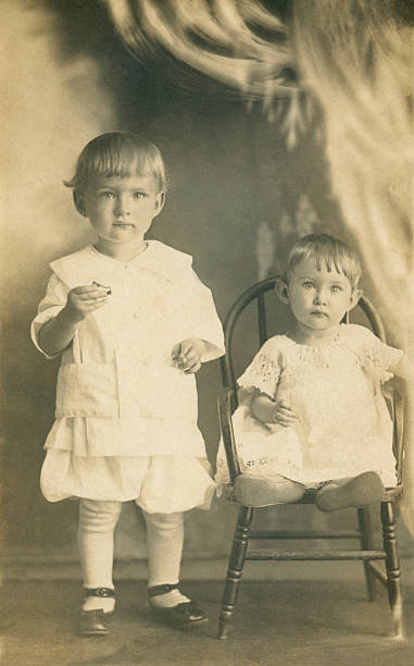 Two Small Children Early 20th Century A brother and sister in the Edwardian Style. Early 20th Century photo restored. 19th century stock pictures, royalty-free photos & images