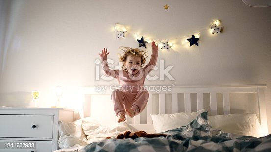 Two small laughing children jumping on bed indoors at home, having fun.
