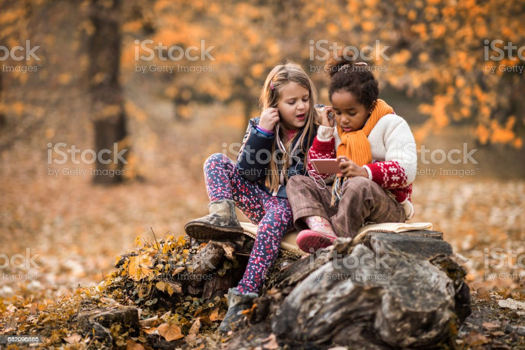 Two small friends listening music on cell phone in nature. stock photo