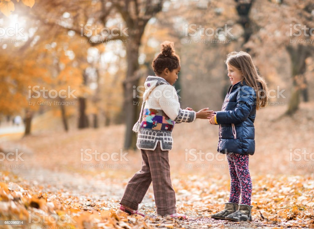 Two small girls spending an autumn day in nature. stock photo