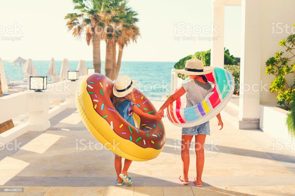 Two small girls with inflatable toys on the beach stock photo