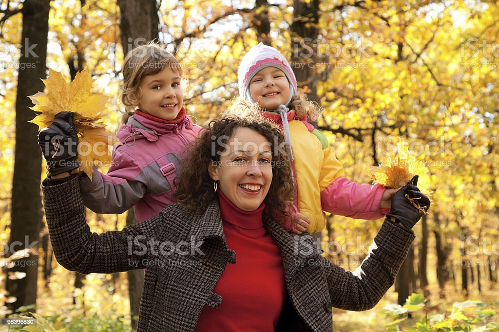 Two small girls with mother in autumnal park royalty-free stock photo