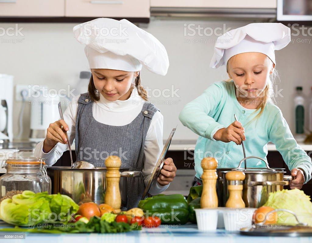 Dois pequenos felizes meninas culinária Sopa de legumes - foto de acervo