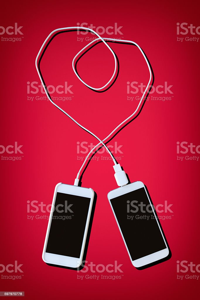 Two Smart Phones Connected Together by Cable Making Heart Shape stock photo