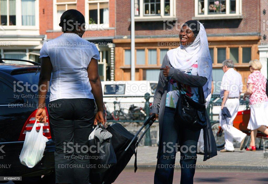 Twee glimlachend Afrikaanse zwarte vrouwen spreken over de straat van Amsterdam foto